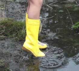 mit Gummistiefel und Regenmantel am See